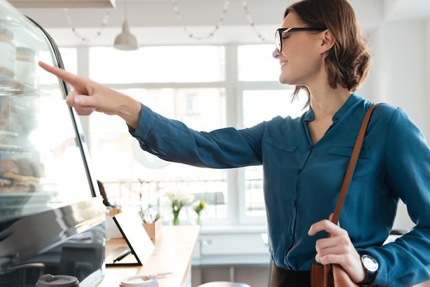 Uśmiechnięta ufna kobiety pozycja przy gablotą wystawową w bufecie