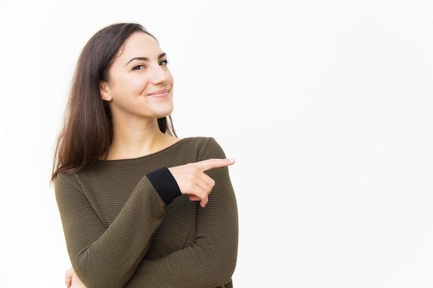 Uśmiechnięta ufna piękna kobieta wskazuje palec wskazującego