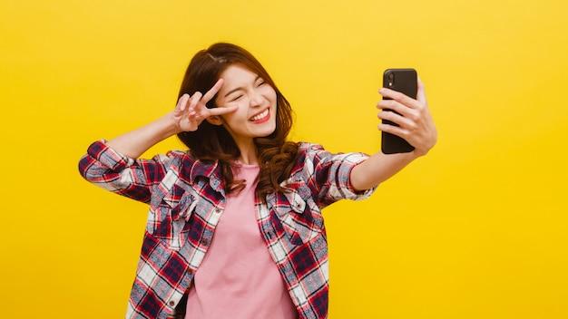 Uśmiechnięta urocza azjatycka kobieta robi selfie fotografii na smartphone z pozytywnym wyrażeniem w przypadkowej odzieży i patrzeje kamerę nad kolor żółty ścianą. szczęśliwa urocza uradowana kobieta cieszy się sukcesem.