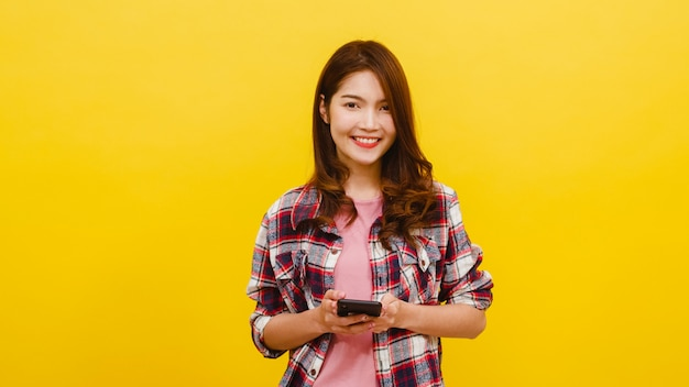 Uśmiechnięta urocza azjatycka kobieta używa telefon z pozytywnym wyrażeniem, uśmiecha się szeroko, ubiera w przypadkowej odzieży i patrzeje kamerę nad kolor żółty ścianą. szczęśliwa urocza uradowana kobieta cieszy się sukcesem.