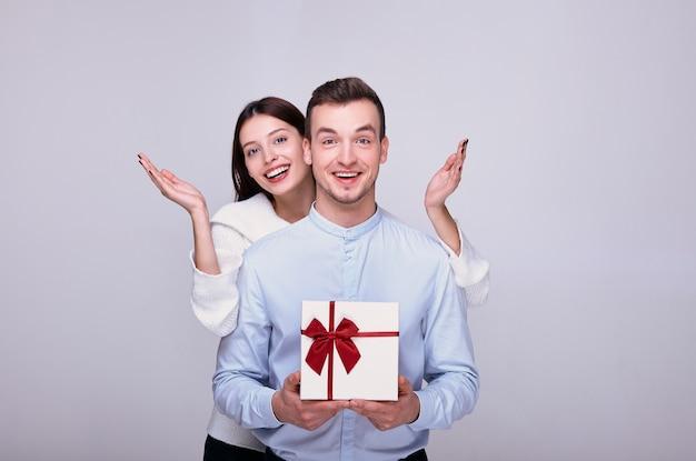 Uśmiechnięta urocza czarująca kobieta z rozłożonymi rękami stoi za uśmiechniętym facetem z prezentem