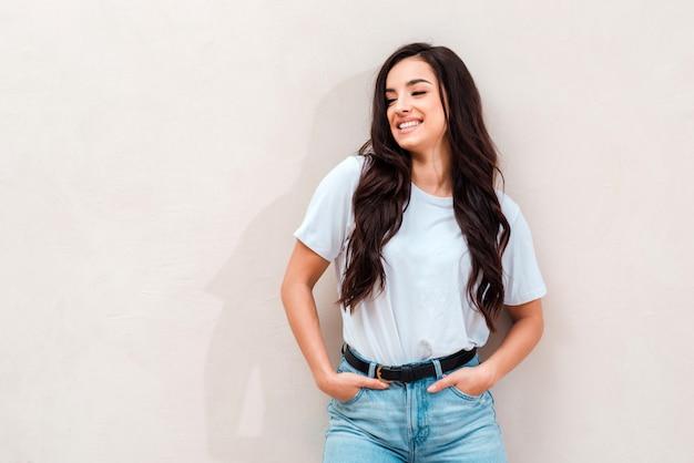 Uśmiechnięta, urocza dziewczyna ubrana w białą koszulkę i dżinsy pozowanie. miejsce na reklamę