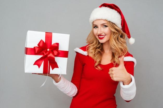 Uśmiechnięta urocza dziewczyna w czerwonym stroju świątecznym trzymająca duże pudełko i pokazująca gest kciuka w górę na szarej powierzchni