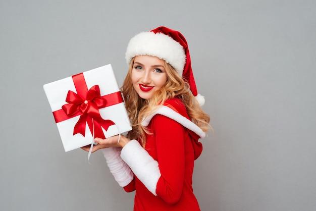 Uśmiechnięta urocza dziewczyna w czerwonym stroju świątecznym trzymająca duże pudełko na prezent na szarej powierzchni