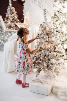 Uśmiechnięta urocza dziewczynka w ślicznej sukni z dużą ilością świątecznych prezentów