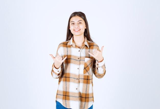 Uśmiechnięta urocza kobieta stojąca na białej ścianie.
