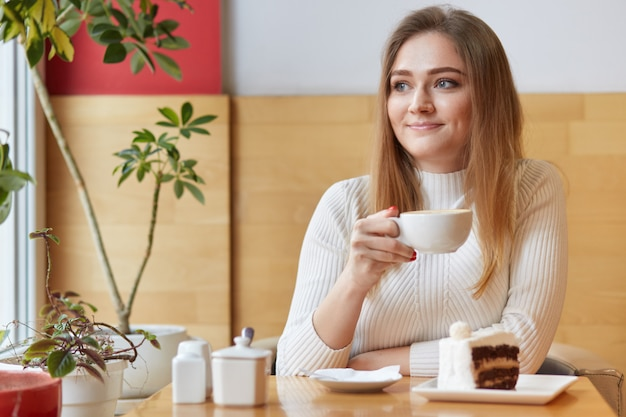 Uśmiechnięta urocza kobieta wygląda przez okno z białą filiżanką gorącego napoju w dłoni, czuje się komfortowo w pomieszczeniu, wygląda marzycielsko i czule