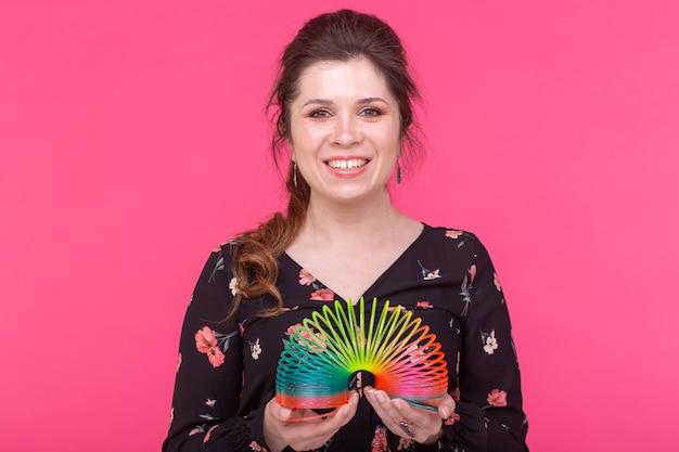 Uśmiechnięta urocza młoda brunetka trzyma w rękach tęczową zabawkę, stojąc na niebieskim tle z miejsca na kopię. koncepcja beztroskiej młodej dziewczyny