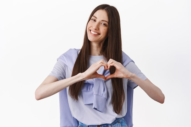 Uśmiechnięta urocza młoda kobieta pokazująca gest serca, przechylająca głowę i wyglądająca uroczo, znak kocham cię, stojąca przy białej ścianie