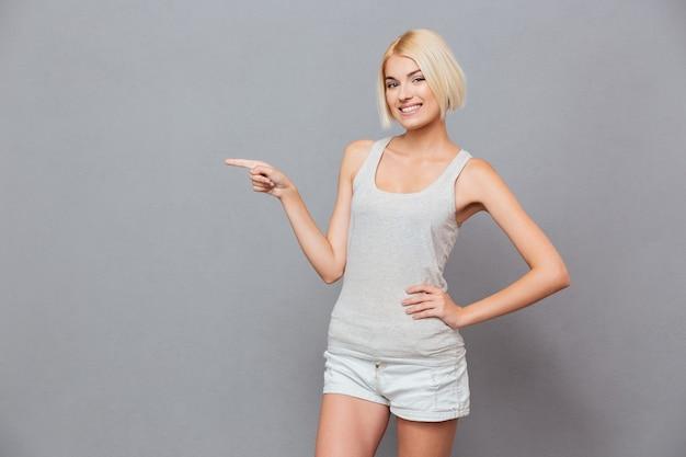 Uśmiechnięta urocza młoda kobieta stoi i wskazuje w bok
