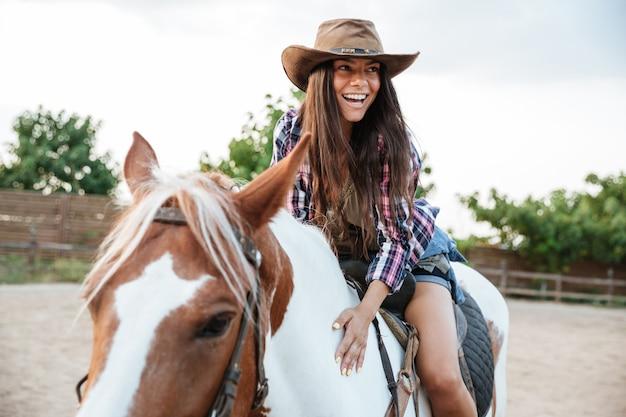 Uśmiechnięta urocza młoda kowbojka womna jedzie na koniu na zewnątrz i śmieje się