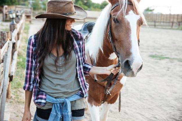 Uśmiechnięta urocza młoda kowbojka z koniem w wiosce