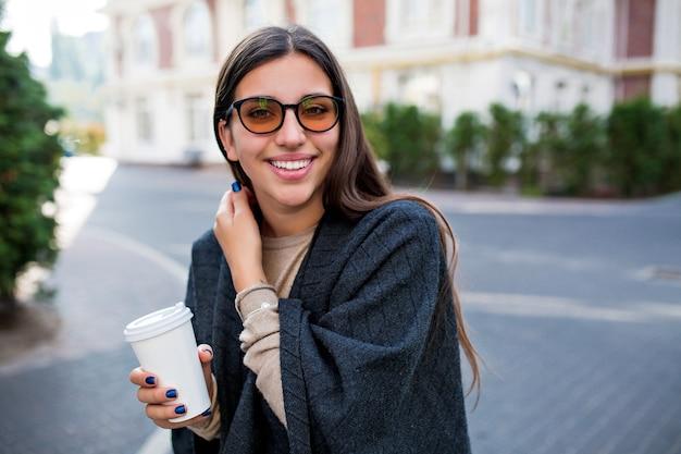Uśmiechnięta urocza nieśmiała kobieta spaceru z kawą na ulicy i cieszy się weekendem w mieście