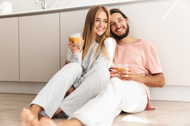Uśmiechnięta urocza para obejmująca się siedząc na podłodze w kuchni i pijąca sok pomarańczowy