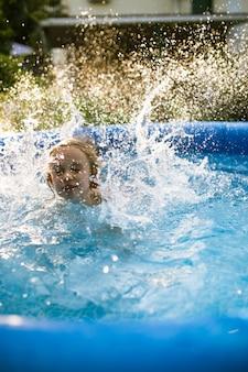Uśmiechnięta urocza siedmioletnia dziewczyna gra i zabawy w nadmuchiwanym basenie.