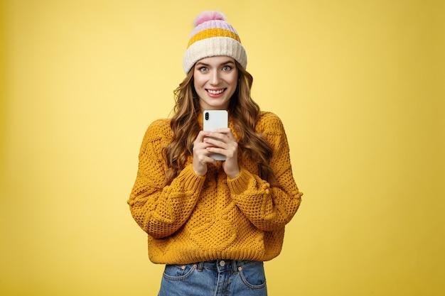 Uśmiechnięta, urocza, urocza młoda, modna dziewczyna trzymająca zupełnie nowy smartfon, usatysfakcjonowana