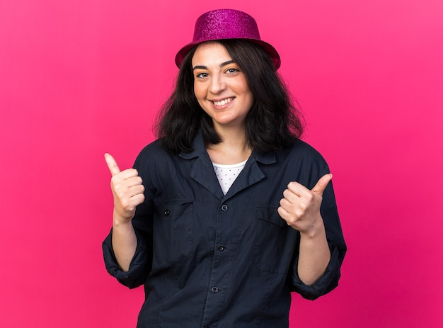 Uśmiechnięta uśmiechnięta młoda kaukaska imprezowa kobieta w kapeluszu imprezowym, patrząca na przód pokazująca kciuki w górę odizolowane na różowej ścianie