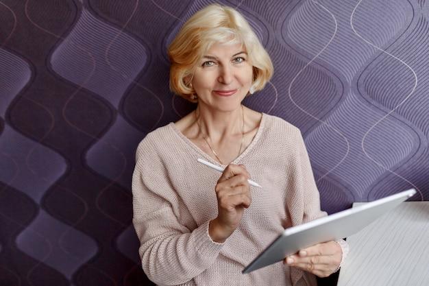 Uśmiechnięta w średnim wieku blond kobieta używa pastylkę