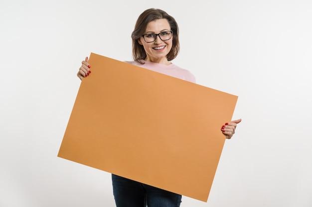 Uśmiechnięta w średnim wieku kobieta z pomarańcze prześcieradła billboardem