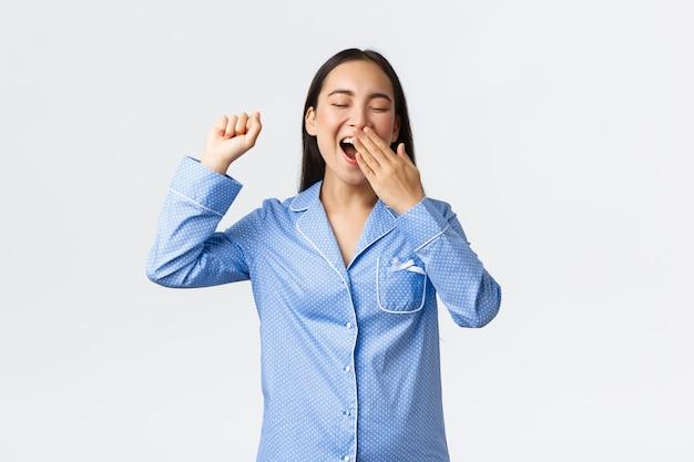 Uśmiechnięta wesoła azjatka w niebieskich dżinsach, ziewająca osłona otworzyła usta dłonią i wyciągnęła ręce po przebudzeniu się rano. dziewczyna gotowa rozpocząć nowy dzień po dobrej drzemce, białe tło