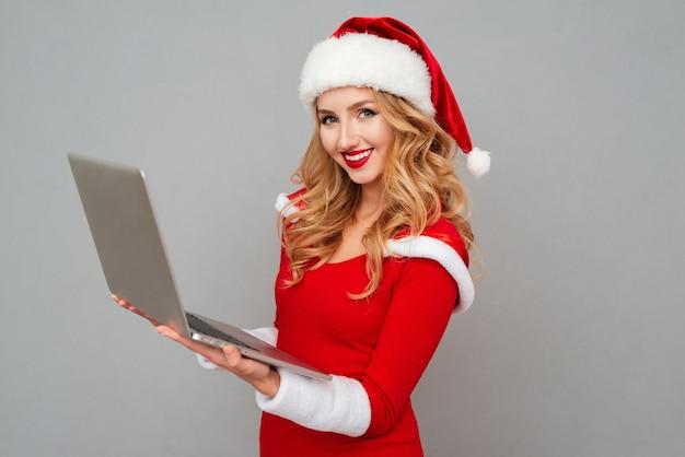 Uśmiechnięta wesoła kobieta w czerwonym stroju świętego mikołaja trzymająca laptopa i patrząca na przód odizolowany na szarej powierzchni