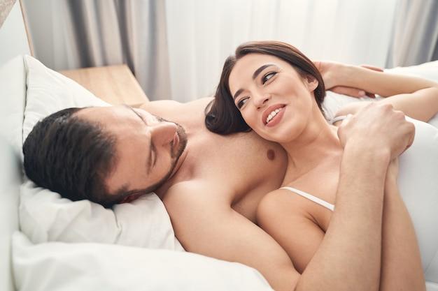 Uśmiechnięta, wesoła, ładna ciemnowłosa kobieta leżąca na piersiach kaukaskich małżonków w łóżku