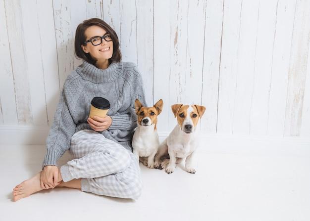 Uśmiechnięta wesoła młoda kobieta nosi ciepły wełniany sweter, kwadratowe okulary, pije gorący napój, relaksuje się na podłodze i jej dwa ulubione zwierzaki