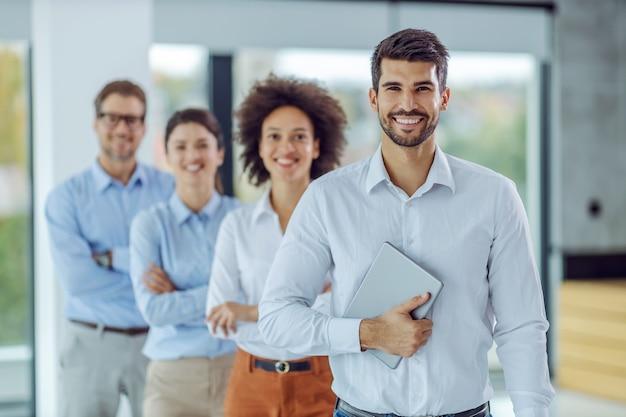 Uśmiechnięta wielokulturowa grupa ludzi biznesu stojących w rzędzie w biurze i patrząc z przodu