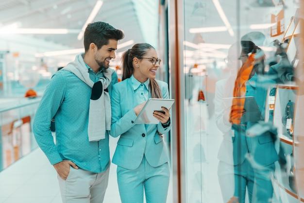 Uśmiechnięta wielokulturowa para ubierał elegancki patrzejący zakupy okno w centrum handlowym.