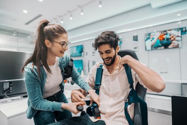 Uśmiechnięta wielokulturowa para wypróbowuje technologię wirtualnej rzeczywistości. mężczyzna siedzi na krześle, podczas gdy kobieta zapina pasek. wnętrze sklepu technicznego.