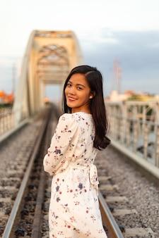 Uśmiechnięta wietnamska kobieta z czarnymi włosami, stojąca na starym moście
