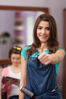 Uśmiechnięta właścicielka salonu fryzjerskiego, wyświetlono znak ręki ok