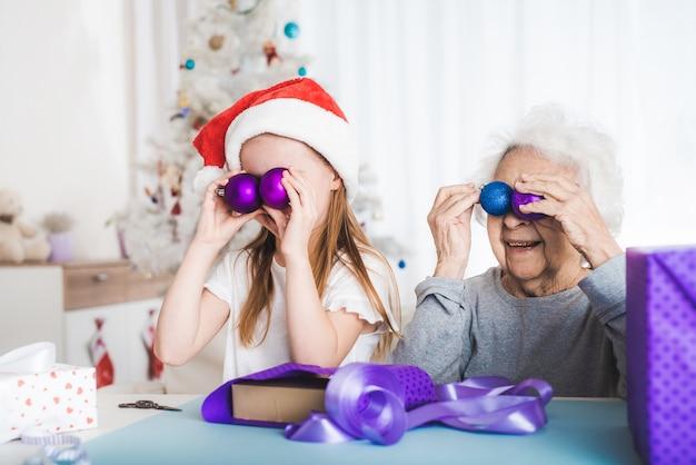 Uśmiechnięta wnuczka w santa hat gra ozdobne kulki na boże narodzenie