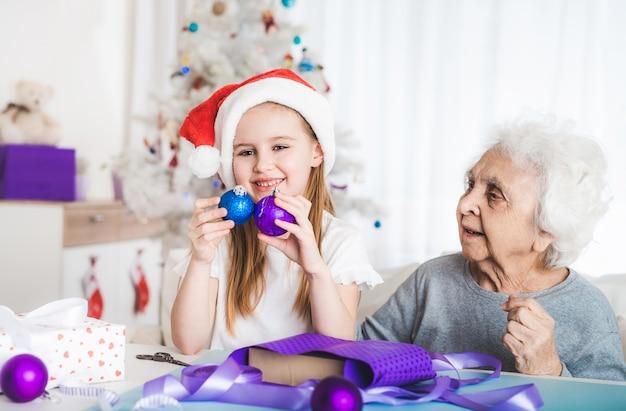 Uśmiechnięta wnuczka w santa hat siedzą z babcią trzymającą ozdobne kulki na boże narodzenie