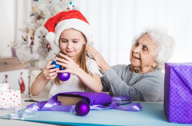 Uśmiechnięta wnuczka w santa hat siedzi z ozdobnymi kulkami na boże narodzenie