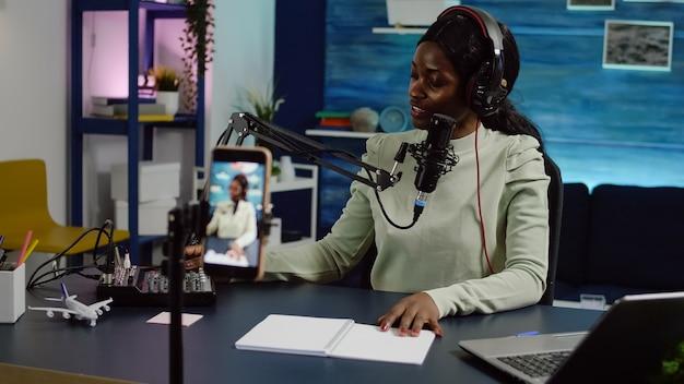 Uśmiechnięta wpływowa afrykańska kobieta siedząca przed kamerą telefoniczną nagrywająca wideo na blogu