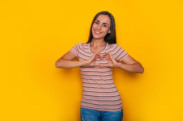 Uśmiechnięta wspaniała kobieta trzyma ręce w kształcie serca i pokazuje ten symbol w aparacie