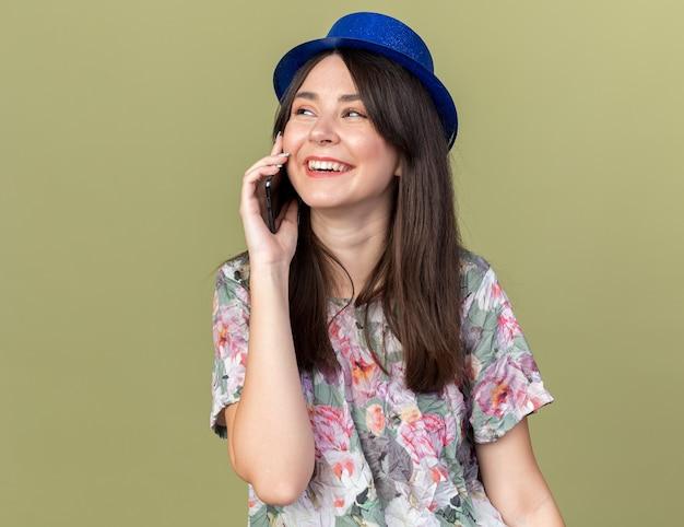 Uśmiechnięta wyglądająca strona młoda piękna dziewczyna w kapeluszu imprezowym mówi przez telefon odizolowany na oliwkowozielonej ścianie