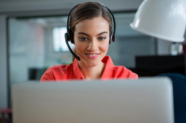 Uśmiechnięta wykonawczy żeński pracuje na swoim laptopie podczas rozmowy
