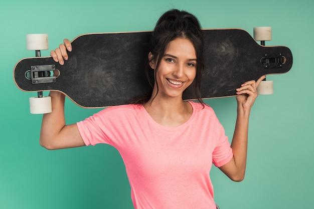 Uśmiechnięta, wysportowana dziewczyna trzyma łyżwę na ramionach. dziewczyna pozuje
