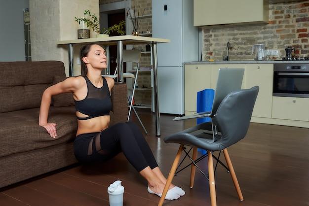 Uśmiechnięta wysportowana dziewczyna w czarnym obcisłym garniturze ćwiczy triceps i klatkę piersiową oraz ogląda na laptopie wideo treningowe online. trenerka prowadząca zdalne zajęcia fitness w domu.