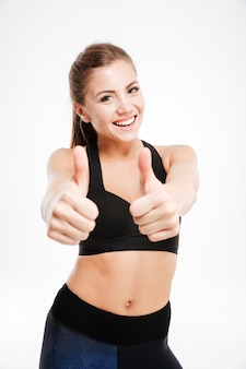 Uśmiechnięta wysportowana kobieta pokazująca kciuk w górę, znak nad
