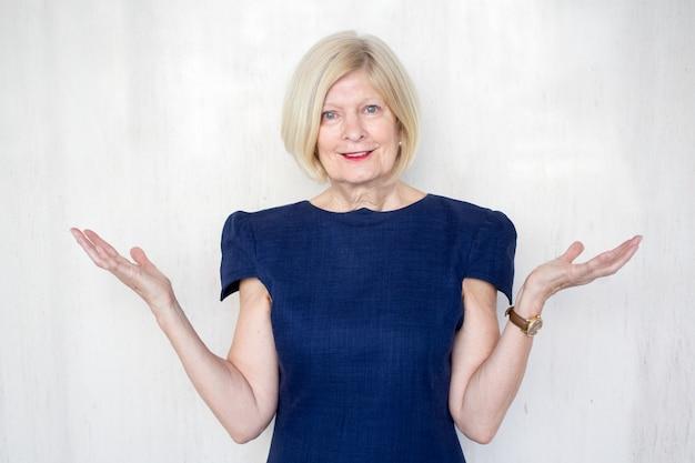 Uśmiechnięta wyższego szczebla businesswoman wzruszając ramiona