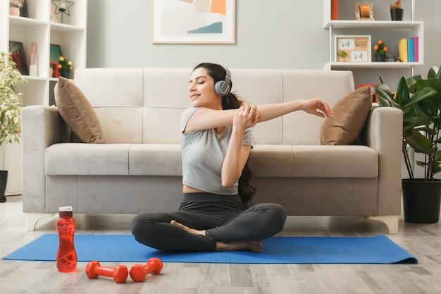 Uśmiechnięta z zamkniętymi oczami młoda dziewczyna w słuchawkach ćwiczących na macie do jogi przed sofą w salonie