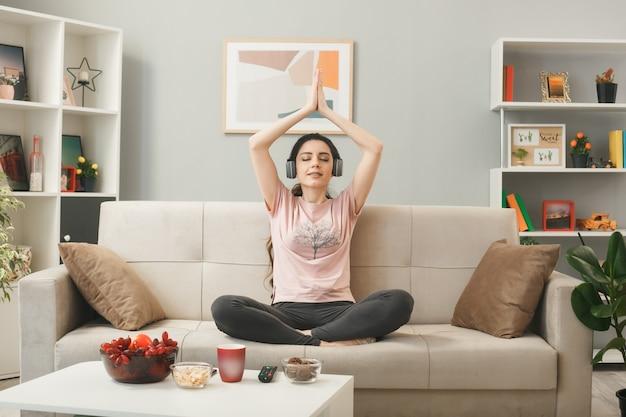 Uśmiechnięta z zamkniętymi oczami młoda dziewczyna w słuchawkach robi joga siedząca na kanapie za stolikiem kawowym w salonie