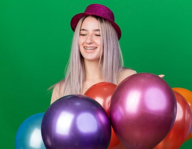 Uśmiechnięta z zamkniętymi oczami młoda piękna dziewczyna w kapeluszu imprezowym i szelkach stojąca za balonami