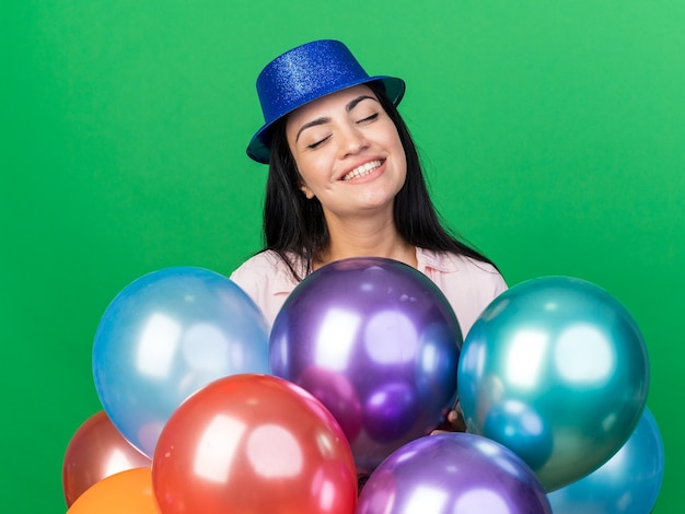 Uśmiechnięta z zamkniętymi oczami młoda piękna dziewczyna w kapeluszu imprezowym stojąca za balonami odizolowanymi na zielonej ścianie