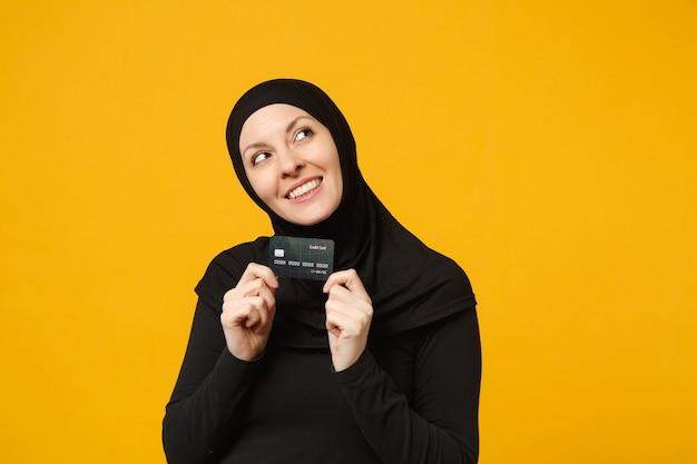 Uśmiechnięta zabawa młoda arabskiej kobiety muzułmańskiej w hidżab czarne ubrania trzymać w ręku karty kredytowej banku na białym tle na portret żółty ściany. koncepcja życia religijnego ludzi.