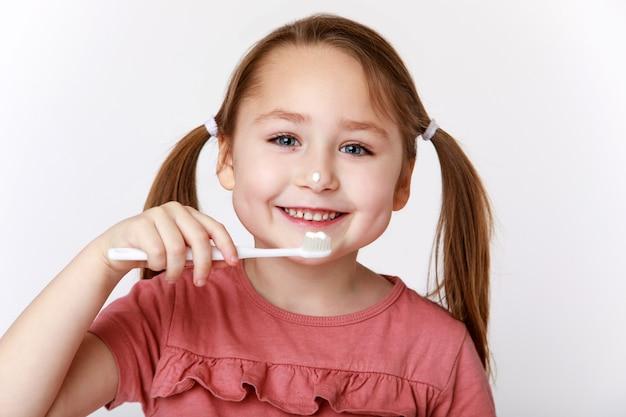 Uśmiechnięta zadowolona dziewczynka podczas mycia zębów
