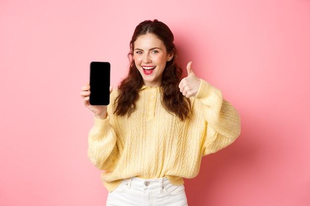 Uśmiechnięta zadowolona kobieta pokazująca kciuki do góry i pusty ekran smartfona, polecająca aplikację lub stronę internetową, stojąca przed różową ścianą.